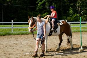 Alli leading a therapy horse named Joe during a week of Autism Camp.