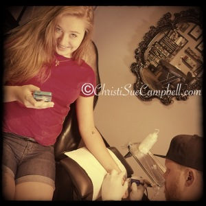 Alli distracts herself with her phone while she is inked. Nothing compares to broken bones and the pain of soccer injuries and physical therapy. This was nuthin.